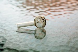 Meth Pipe on a Glass Table Top Signifying Methamphetamine Abuse