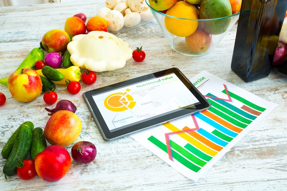 Nutrition Symbolized by Fruits and Vegetables on a Counter with an Electronic Tablet and Printed out Charts