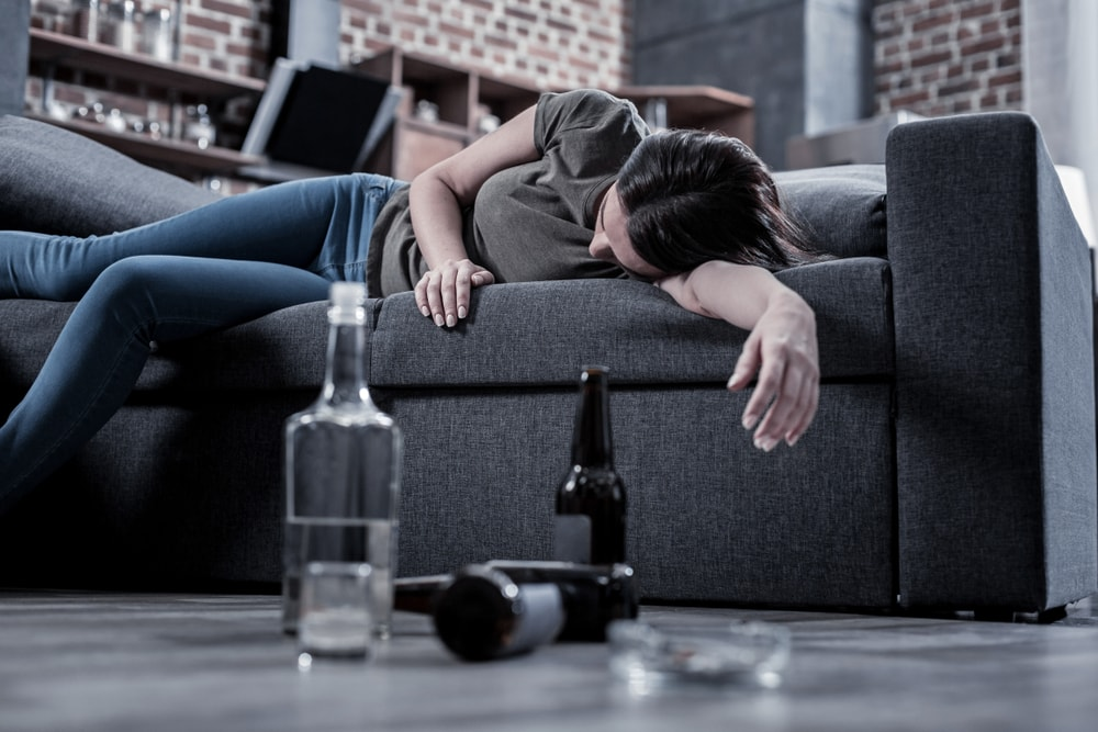 Alcohol Addiction Depicted by a Woman Passed Out on a Couch With a Bottle of Liquor and Empty Beer Bottles Scattered on the Floor