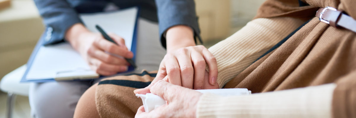 Psychologist holding female patient's jand