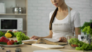 Asian woman reading cooking book and choosing dinner recipe, healthy food habit, stock footage