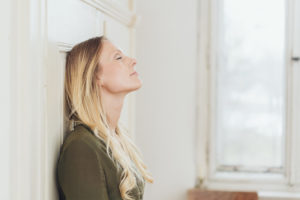 Woman Standing with eyes closed being mindful